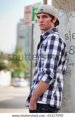 Young man in an urban lifestyle fashion pose leaning against a city utility pole wearing a hat. - stock photo