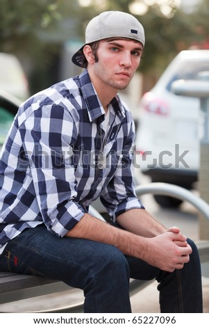 Young man in an urban lifestyle fashion pose sitting on a street bench wearing a hat. - stock photo