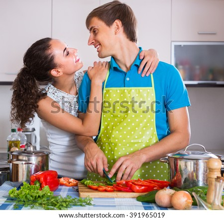 Young man in apron helping smiling wife to prepare healthy dinner