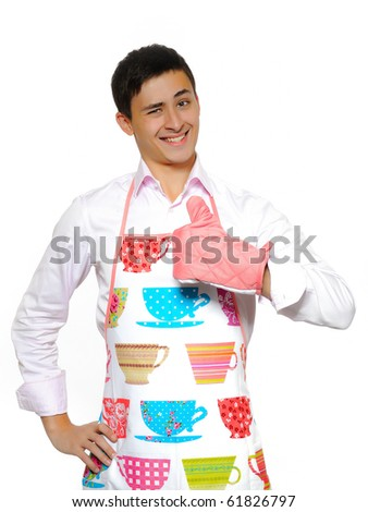 Young man in apron preparing to cook romantic dinner - stock photo