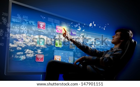 Young man in armchair pushing icon on media screen - stock photo