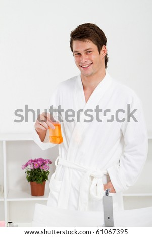 young man in bathroom with mouth wash bottle - stock photo