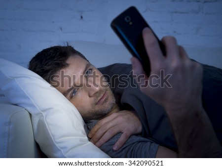 young man in bed couch at home late at night using mobile phone in low light relaxed in communication technology and internet social network concept - stock photo