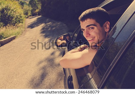 Young man in black car ready for trip looking at the view - stock photo