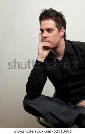 Young man in black clothes sitting on a chair and thinking - stock photo