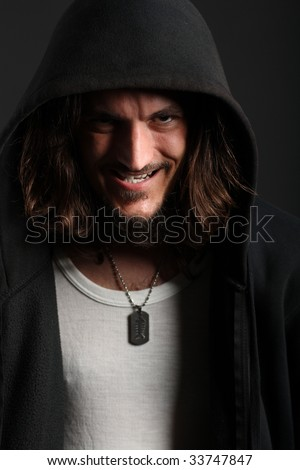 Young man in black hood with cheeky grin on black background