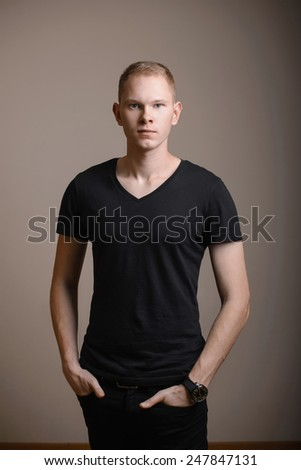 Young man in black shirt in the studio - stock photo