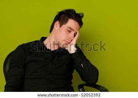 Young man in black shirt sleeping in chair - stock photo