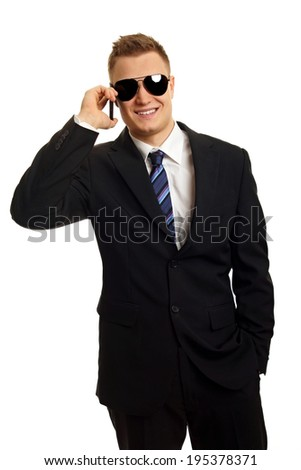 Young man in black suit and sunglasses talks into the mobile phone - stock photo