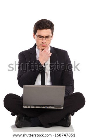 Young man in black suit holds laptop on his crossed legs and thinking. Full length studio shot isolated on white. - stock photo