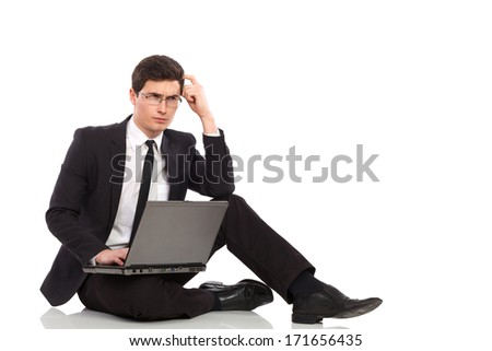 Young man in black suit holds laptop on his leg, thinking and scratching head. Full length studio shot isolated on white.