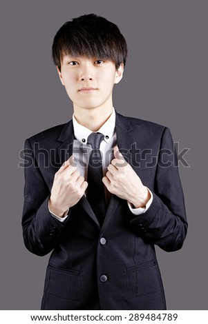 Young man in black suit on black background