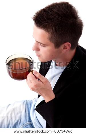 Young man in black suit with cup of tea - stock photo