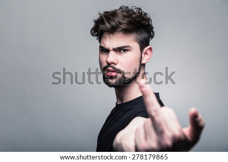 Young man in  black T-shirt shows gesture - stock photo