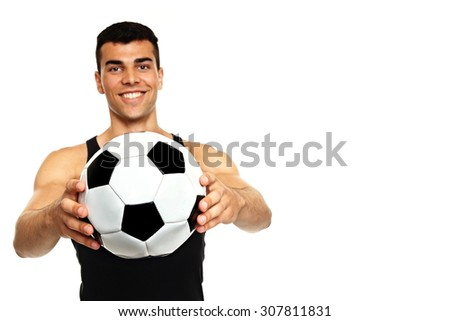 Young man in black undershirt holds soccer ball, focus is on ball - stock photo