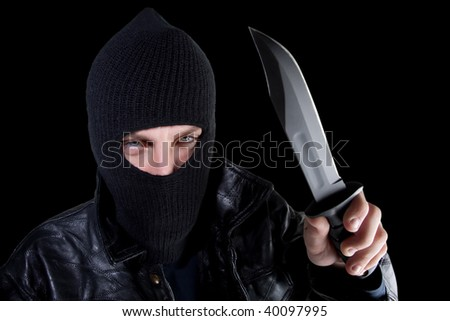 Young man in black with large knife - stock photo