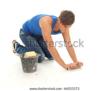 young man in blue, casual shirt cleaning floor - stock photo
