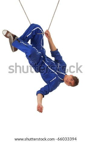 young man in blue coveralls in acrobatic tricks on rope - stock photo