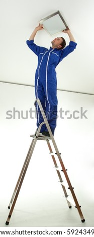 young man in blue coveralls on ladder attaching lamp - stock photo