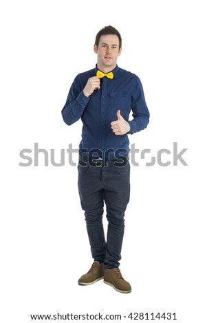 Young man in blue shirt and yellow bow-tie showing his thumb up