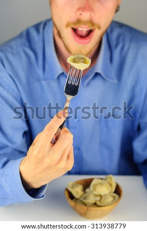 Young man in blue shirt eats dumplings with meat