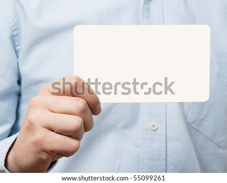Young man in blue shirt holding a blank white card - stock photo