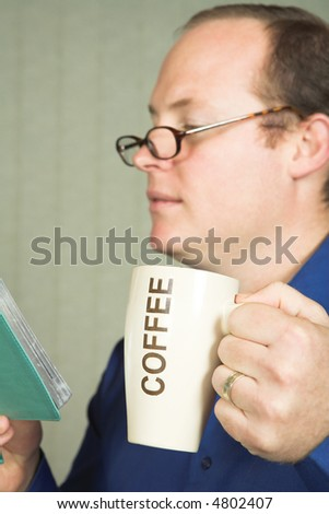 Young man in blue shirt holding coffee mug and reading a book through glasses. Focus on hand with coffee