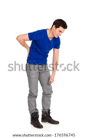 Young man in blue shirt holding lower back in pain. Full length studio shot isolated on white. - stock photo