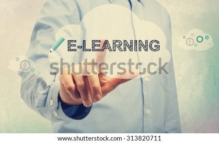 Young man in blue shirt pointing at E-Learning text - stock photo