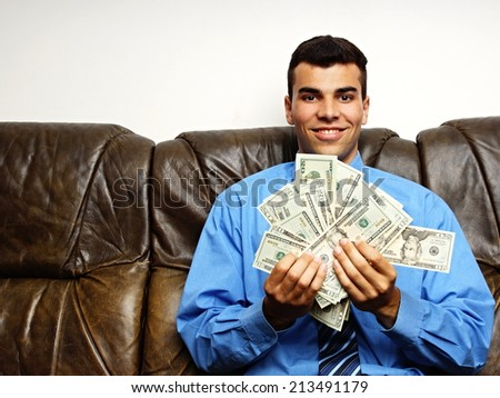 Young man in blue shirt shows you money, left you can write some text - stock photo