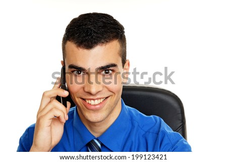 Young man in blue shirt talks into the mobile phone - stock photo