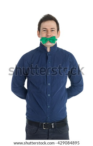 Young man in blue shirt with green bow-tie in his mouth