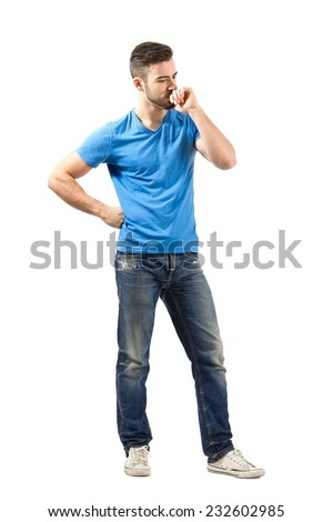 Young man in blue t-shirt thinking looking down. Full body length isolated over white background. - stock photo