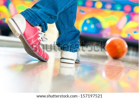 Young man in bowling alley having fun, the sporty man playing a bowling ball in front of the tenpin alley - stock photo