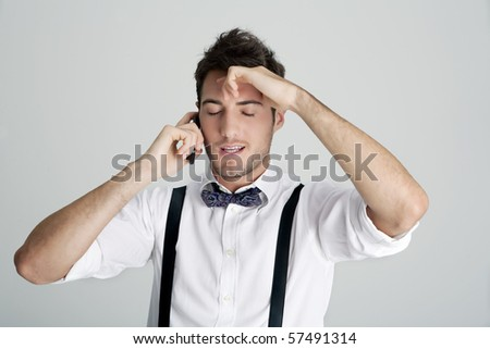 Young man in bowtie and suspenders on the phone and frustrated, studio shot - stock photo