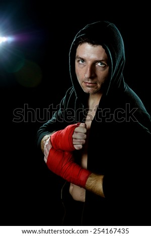 young man in boxing hoodie jumper with hood on head wearing hand and wrist wrapped ready for fighting posing isolated on black background with angry face expression - stock photo