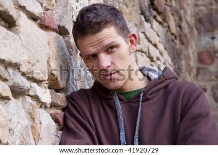 Young man in brown sweatshirt next to the brick wall
