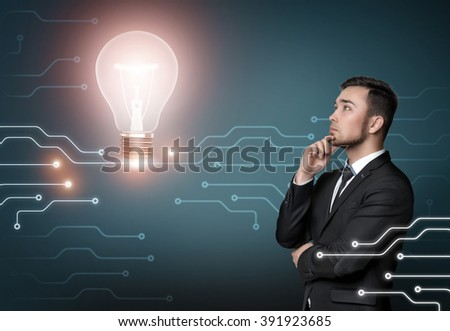 Young man in business suit thinking about idea, on concrete wall background. Shining light bulb. Business concept - stock photo