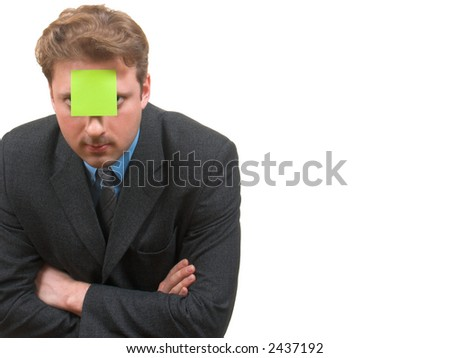Young man in business suit with a sticky note attached to his forehead bend forward to camera with a copyspace beside him - stock photo