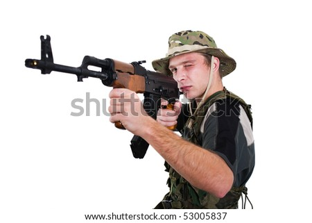 Young man in camouflage aiming with a Kalshnikov rifle.