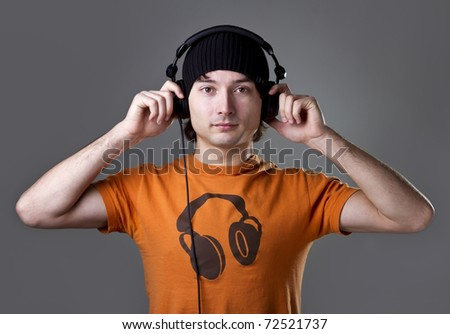 Young man in cap with headphones on gray background