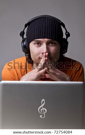 Young man in cap with headphones on gray background - stock photo