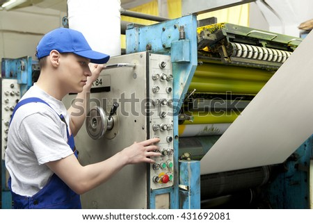 Young man in cap working in newspaper factory