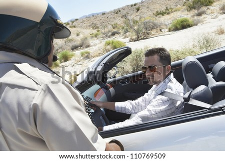 Young man in car looking at policeman - stock photo