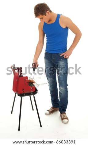 young man in casual blue shirt grilling chicken - stock photo