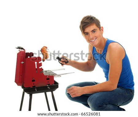 young man in casual blue shirt grilling chicken