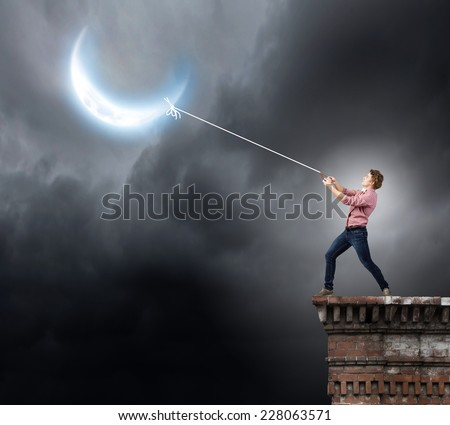 Young man in casual catching moon with rope - stock photo