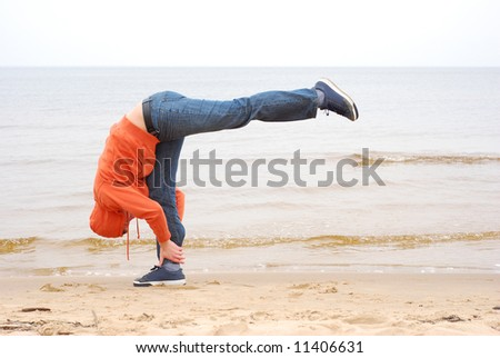 Young man in casual clother doing yoga on the seaside