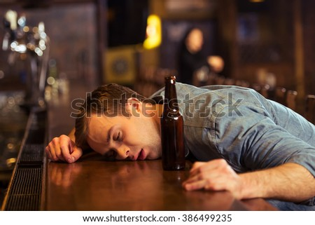 Young man in casual clothes is sleeping near the bottle of beer on a bar counter in pub - stock photo