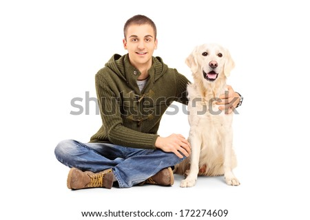 Young man in casual clothes sitting on floor with his Labrador retriever dog isolated on white background - stock photo